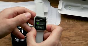 Setting new Apple Watch wearable smartwatch computer. PARIS, FRANCE - CIRCA 2018: POV man unboxing unpacking latest Apple Watch Series 3 GPS LTE smartwatch stock footage