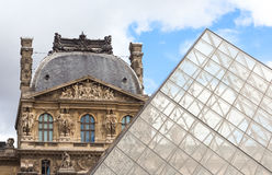 PARIS / FRANCE - CIRCA SEPTEMBER 2012 - The Louvre pyramid is pictured contrasting with the Louvre museum in the background Royalty Free Stock Photography
