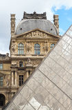 PARIS / FRANCE - CIRCA SEPTEMBER 2012 - The Louvre pyramid is pictured contrasting with the Louvre museum in the background Royalty Free Stock Image