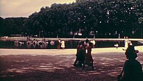 Paris 1970s Versailles fountain. PARIS, FRANCE - CIRCA 1976: Tourists looking the Quadriga statue in the Apollo fountain at Palace of Versailles garden. Historic stock video footage