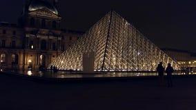 PARIS, FRANCE - DÉCEMBRE, 31, 2016 Les touristes silhouette près de la pyramide en verre de Louvre la nuit Musée français célèbre banque de vidéos