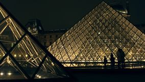 PARIS, FRANCE - DÉCEMBRE, 31, 2016 Les touristes silhouette près de la pyramide en verre de Louvre la nuit Musée français célèbre Images stock