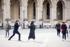 Paris, France 29 de março de 2018 Homem novo que toma a foto de sua amiga perto do museu do Louvre imagens de stock royalty free