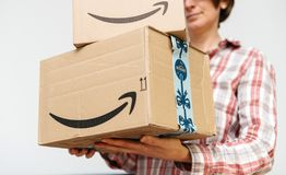 Woman with Amazon Prime cardboard parcels in hands stock images