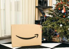 Amazon Cardboard box near Christmas tree in the living room. PARIS, FRANCE - DEC 26, 2018: Freshly received Amazon Prime parcel cardboard box near Christmas tree royalty free stock photo