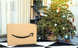 Amazon Cardboard box near Christmas tree in the living room. PARIS, FRANCE - DEC 26, 2018: Large freshly received Amazon Prime parcel cardboard box near stock photography