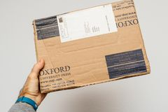 Man holding parcel with books from Oxord Univeristy press Royalty Free Stock Images