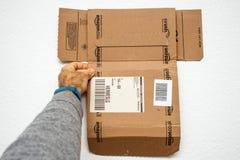 Man holding new Amazon Prime cardboard box. PARIS, FRANCE - DEC 18, 2017: Man holding new Amazon Prime cardboard box against white background Stock Image