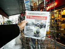 French newspaper kiosk selling. PARIS, FRANCE - DEC 10, 2018: Newspaper stand kiosk stand selling press with male hand buying latest l`Humanite edition featuring royalty free stock image