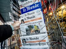 French newspaper kiosk selling. PARIS, FRANCE - DEC 10, 2018: Newspaper stand kiosk stand selling press with male hand buying latest Le monde featuring Gilets royalty free stock photo