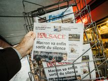 French newspaper kiosk selling about latest events in France. PARIS, FRANCE - DEC 10, 2018: Newspaper stand kiosk stand selling press with male hand buying royalty free stock images