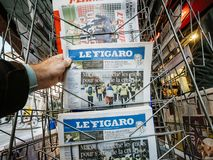 French newspaper kiosk selling latest Le Figaro man buy news pol. PARIS, FRANCE - DEC 10, 2018: Newspaper stand kiosk stand selling press with man hand buying Le stock image