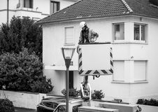 Worker cleaning repairing changing the light tube of a light mas. PARIS, FRANCE - DEC 16, 2017:  Worker cleaning repairing changing the light tube of a light Royalty Free Stock Image