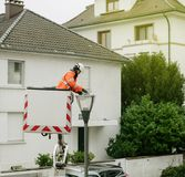 Worker in protection suit cleaning repairing changing the light. PARIS, FRANCE - DEC 16, 2017: Worker in protection suit cleaning repairing changing the light Stock Image