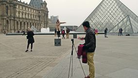 PARIS, FRANCE - DECEMBER, 31. Asian and European tourists taking photos near the Louvre, famous French museum. Popular stock photos