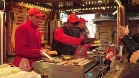 PARIS, FRANCE - DECEMBER, 31. Christmas and New Year market fastfood stall vendors at work. Cheerful black man giving. Burger Stock Photography