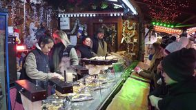 PARIS, FRANCE - DECEMBER, 31. Christmas and New Year market fastfood stall vendors at work. Traditional cheese. PARIS, FRANCE - DECEMBER, 31. Christmas and New Royalty Free Stock Image