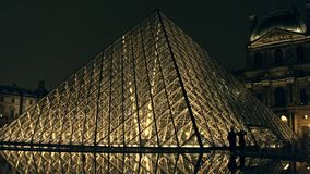 PARIS, FRANCE - DECEMBER, 31, 2016. Couple silhouettes near glass Louvre pyramid at night. Famous French museum and Stock Photos