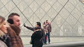 PARIS, FRANCE - DECEMBER, 31. Couples making selfies near the Louvre glass pyramid, famous French museum and popular Stock Image