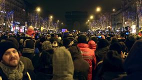 PARIS, FRANCE - DECEMBER, 31, 2016. Crowded Champs-Elysees street and light show on famous triumphal arch, Arc de stock video footage