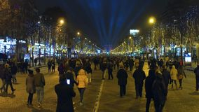 PARIS, FRANCE - DECEMBER, 31, 2016. Crowded decorated Champs-Elysees street and distant famous triumphal arch, Arc de Stock Image
