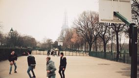 PARIS, FRANCE - DECEMBER, 31, 2016. Multinatonal male teenagers playing street basketball against Eiffel Tower on a stock video footage