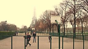 PARIS, FRANCE - DECEMBER, 31, 2016. Multinatonal male teenagers playing street basketball against Eiffel Tower on a stock footage