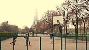 PARIS, FRANCE - DECEMBER, 31, 2016. Multinatonal male teenagers playing street basketball against Eiffel Tower on a Stock Photo