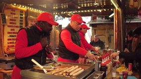 PARIS, FRANCE - DECEMBER, 31, 2016. New Year market fastfood stall vendors. Black and caucasian cooks at work. PARIS, FRANCE - DECEMBER, 31. New Year market Royalty Free Stock Photos