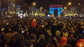 PARIS, FRANCE - DECEMBER, 31, 2016. Overhead pan shot of crowded Champs-Elysees street and light show on famous. Triumphal arch, Arc de Triomphe. New Year`s eve stock footage