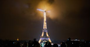 Paris, France - December 23, 2017: People are looking at the Eiffel tower illuminated at night. royalty free stock image