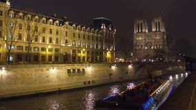 PARIS, FRANCE - DECEMBER, 31, 2016. Seine river touristic boat and the western facade of famous Notre Dame cathedral stock video footage