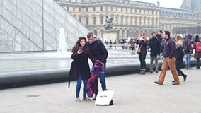 PARIS, FRANCE - DECEMBER, 31, 2016. Steadicam shot of couple making selfie near the Louvre glass pyramid and fountains stock footage