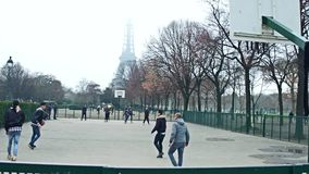 PARIS, FRANCE - DECEMBER, 31, 2016. Steadicam shot of multinatonal teenagers playing street basketball against Eiffel stock video