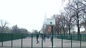 PARIS, FRANCE - DECEMBER, 31, 2016. Steadicam shot of multinatonal teenagers playing street basketball against Eiffel stock footage