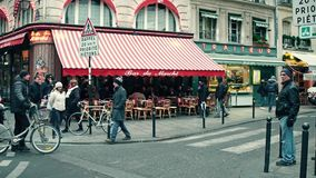 PARIS, FRANCE - DECEMBER, 31, 2016. Steadicam shot of Parisian cafe with awning and urban traffic at road intersection