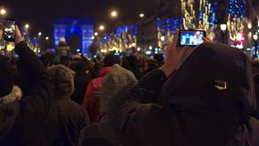 PARIS, FRANCE - DECEMBER, 31, 2016. Tourists making photos of New Year light show near famous triumphal arch, Arc de stock video footage