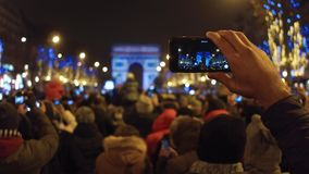 PARIS, FRANCE - DECEMBER, 31, 2016. Tourists recording videos and shooting photos of New Year light show near famous stock footage