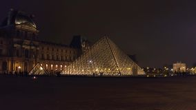 PARIS, FRANCE - DECEMBER, 31, 2016. Tourists silhouettes near glass Louvre pyramid at night. Famous French museum and Royalty Free Stock Photos