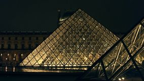 PARIS, FRANCE - DECEMBER, 31, 2016. Tourists silhouettes near glass Louvre pyramid at night. Famous French museum and stock video footage