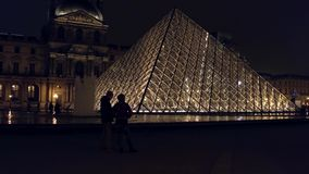 PARIS, FRANCE - DECEMBER, 31, 2016. Tourists silhouettes near glass Louvre pyramid at night. Famous French museum and Stock Photo