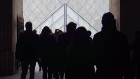 PARIS, FRANCE - DECEMBER, 31, 2016. Tourists silhouettes walking near the Louvre glass pyramid. Popular French museum Royalty Free Stock Photo