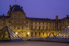 Iew of famous Louvre Museum with Louvre Pyramid at evening Royalty Free Stock Image