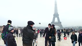 PARIS, FRANCE - DECEMBER, 31, 2016. Young couple posing near Eiffel Tower on a foggy day. The most popular French Stock Image