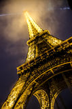 Paris France Eiffel Tower Tourism - Rain and Lgiht. Eiffel Tower in Paris, France lit up in the rain and fog Royalty Free Stock Images