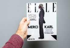 Man holding Elle magazine featuring cover Karl Lagerfeld death. Paris, France - Feb 23, 2019: Man showing French Elle tribute magazine covering Karl Lagerfeld stock photography