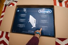 Man unboxing heating convecter DeLonghi from Amazon. PARIS, FRANCE - FEB 7, 2018: Man unboxing large cardboard box containing italian DeLonghi air convection stock photos