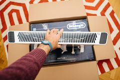 Man unboxing heating convecter DeLonghi from Amazon. PARIS, FRANCE - FEB 7, 2018: Man unboxing large cardboard box containing italian DeLonghi air convection Royalty Free Stock Image