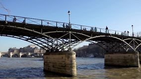 People walking on Pont des Arts and boat traffic - Paris, France