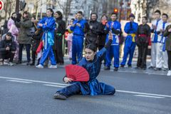 Woman Performing Martial Arts - Chinese New Year Parade, Paris 2. Paris, France-February 25,2018: Woan performing martial arts with a red fan in the street Royalty Free Stock Image